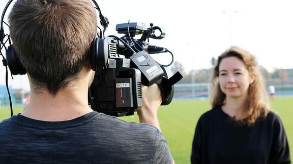 Eine Frau steht nah vor einer Fernsehkamera und wird gefilmt.