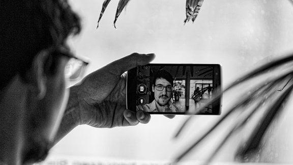Ein junger Mann macht mit dem Smartphone ein Selbstporträt und wird dabei fotografiert.