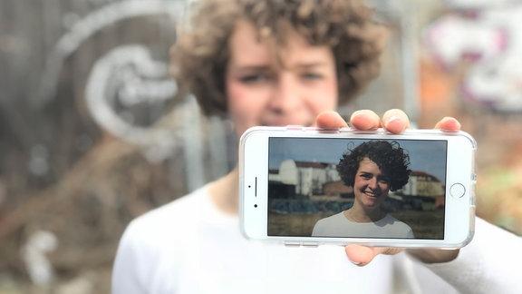 Pia Uffelmann hält ein Smartphone mit einem Bild vor ihr Gesicht.