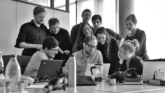 Eine Gruppe Volontäre vor einem Laptop schaut sich Fotos an