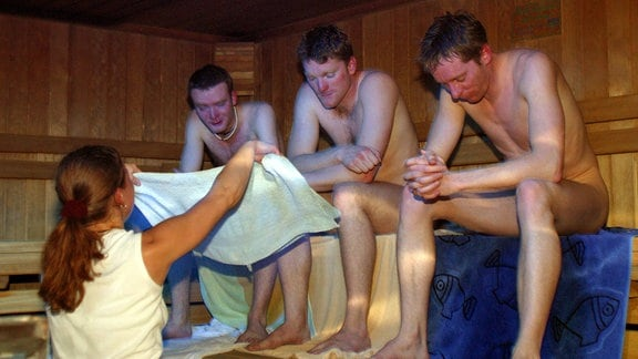 Drei Männer in einer Sauna bekommen eunen Aufguss