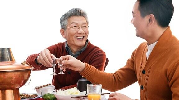 Zwei chinesische Männer trinken Schnaps