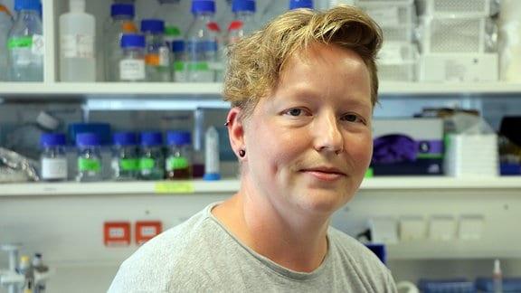 Eine Wissenschaftlerin vor Regalen in ihrem Labor