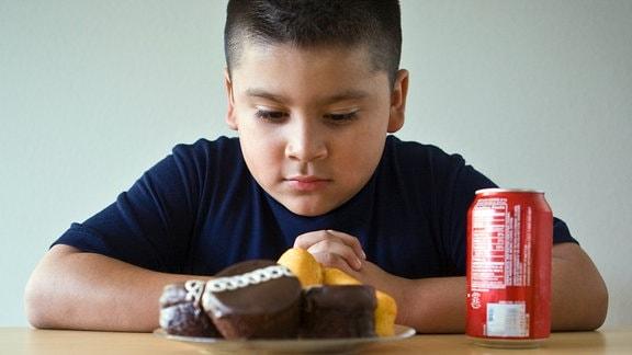 Kleiner Junge mit Cola und Fast Food