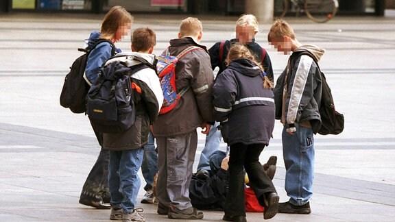Gewalt auf dem Schulhof - Schülergruppe tritt einen wehrlos am Boden liegenden Jungen