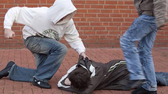 Schlägerei auf dem Schulhof. Ein am Boden liegender wehrloser Junge wird von zwei anderen brutal festgehalten und getreten (gestellte Szene)