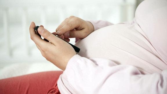Schwangere mit Handy