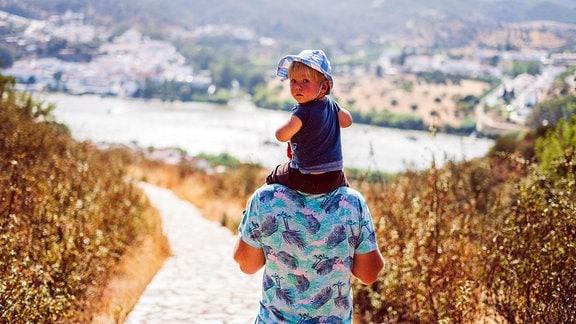 Vater spaziert mit seinem Kind auf den Schultern