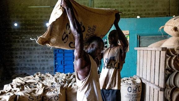 Ein Arbeiter hilft in einem Raum einem anderen Arbeiter, einen schweren Sack mit Kakaobohnen auf den Rücken zu heben, im Hintergrund viele weitere Säcke.