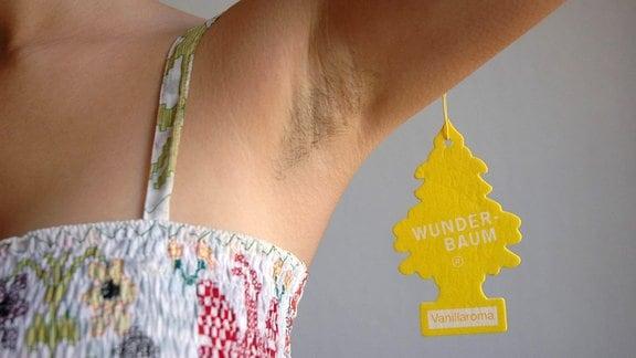 Achselhöhle einer Frau mit Top (Bildausschnitt ohne Gesicht) mit einem Wunderbaum, der nahe der Achsel hängt. Wunderbaum = flache Baumform, das für Raumduft häufig am Rückspiegel in Autos zu finden ist.