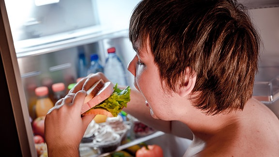 Ein dicker Junge steht vor einem offenen Kühlschrank und beißt in ein Sandwich
