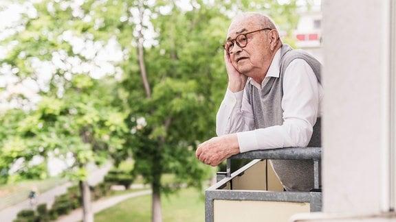 Senior schaut von einem Balkon aus in die Ferne