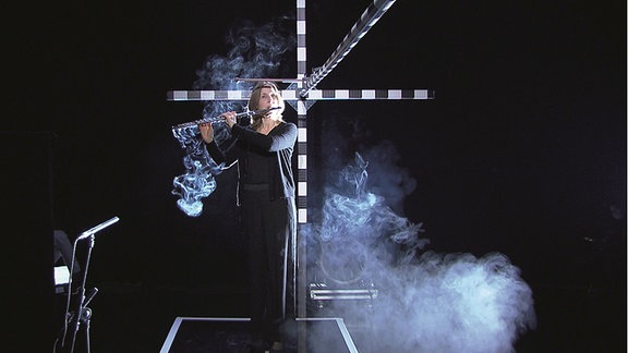 Frau spielt in einem schwarzen Raum Querflöte in einem Versuchsaufbau. Aerosole wurden wie Nebeldampf sichtbar gemacht