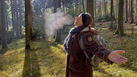 Eine Frau atmet in einem Wald aus.