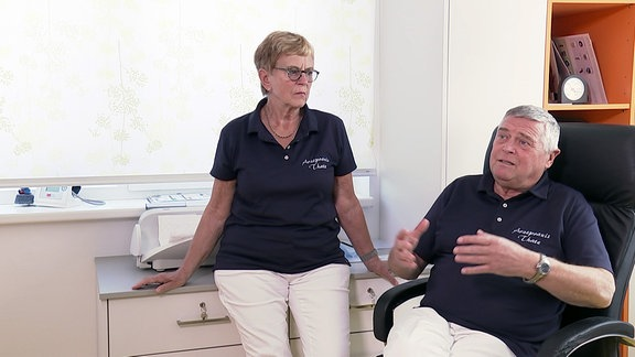 Frau neben Mann auf Stuhl