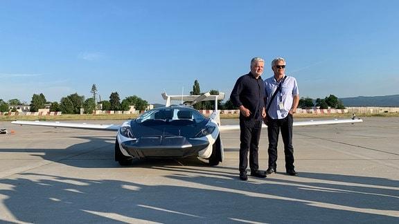 Zwei Männer vor einem Auto das fliegen kann