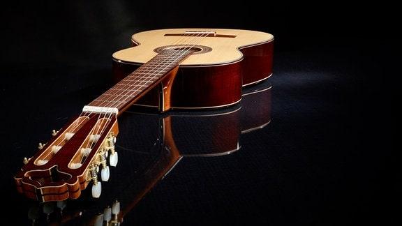 Eine Akustik-Gitarre auf schwarzem Untergrund.