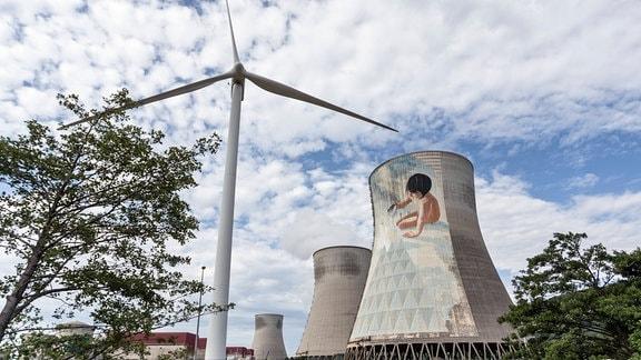 Kernkraftwerk im französischen Cruas: Zwei Kühltürme mit Illustration von spielendem Kind, davor ein Windrad und Baum.