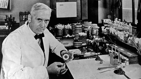Der Mediziner Alexander Flemming sittzt in einem Weißen Kittel an einem Arbeitsplatz, auf dem diverse Flässchchen, Ampullen und Gerätschaften stehen.