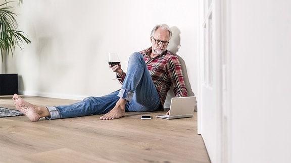 Ein Mann sitzt auf dem Boden und trinkt ein Glas Wein