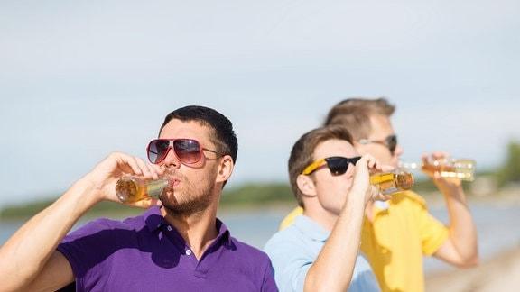 Drei junge Männer trinken aus Flaschen.