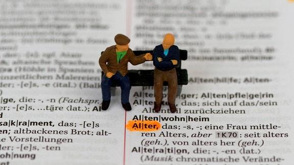 Zwei Seniorenfiguren sitzen auf dem Eintrag des Begriffs Alter im deutschen Duden