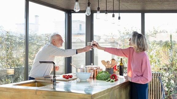 Älteres Paar stößt über Küchentheke hinweg miteinander an.