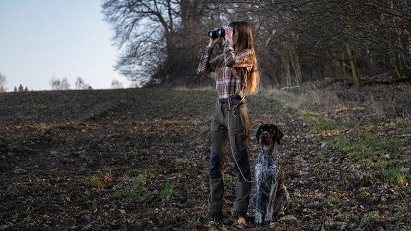 Jägerin Anna Kluger blickt mit einem Fernglas über ein Feld, neben ihr sitzt ihr Jagdhund.