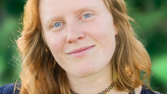 Junge Frau mit hellroten, schulterlangen Haaren, freundlichen blau-grauen Augen und einem leichtem Lächeln. Hält den Kopf etwas geneigt.