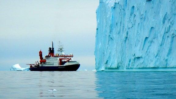 Ein Schiff fährt an einer Wand aus Eis vorbei