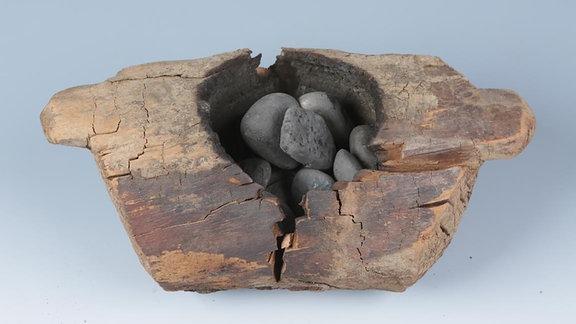 Ein typisches hölzernes Räuchergefäß und verbrannte Steine aus dem Pamir-Gebirge. Das Räuchergefäß ist rund 2500 Jahre alt.