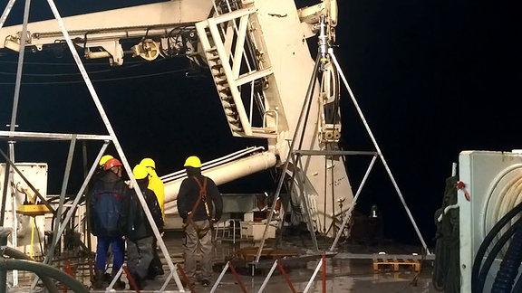 Mehrere Männer mit Schutzhelmen stehen auf dem Deck eines Schiffes neben mehreren Metern hohen technischen Geräten in Form einer Pyramide.