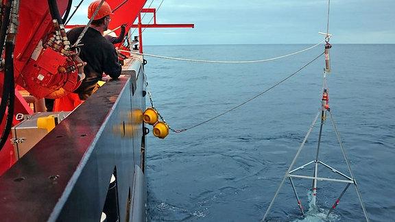 Ein technisches Gerät in Form einer Pyramide wird von einem Schiff aus ins Meer gelassen.