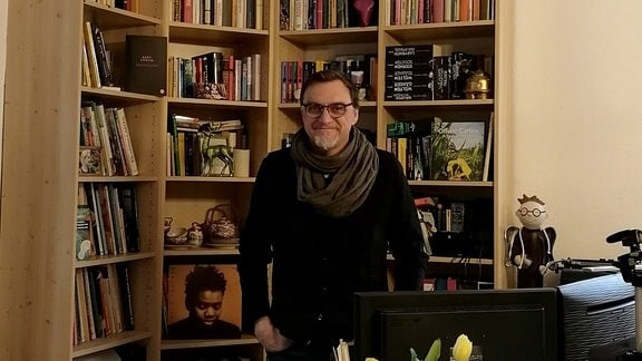 Ein Mann steht neben seinem Schreibtisch im Arbeitszimmer und schaut lächelnd in die Kamera.