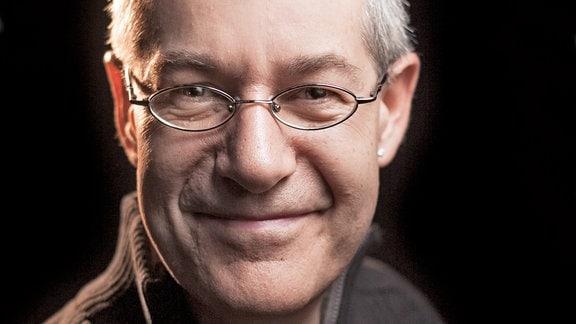 Freundlich die Leser anlächelnder Mann mit angegrautem Haar und länglich ovaler Brille, der einen braunen Pullover trägt.