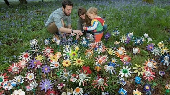 Ein junges Paar und ein kleines Kind knien auf einer Blumenwiese.