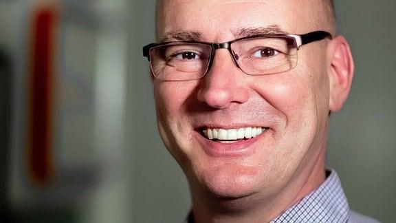 Ein freundlich lächelnder Mann in einem karierten Hemd mit Stirnglatze und eckinger, an der Unterseite randloser Brille.