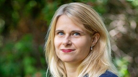 Bild von Frau mit blonden langen Haaren in einem blauen Blazer, die sich mit einem Blick nach links in die Kamera dreht.