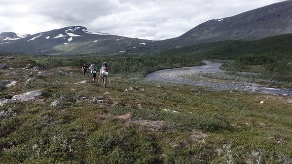 Drei Personen mit Rucksack wandern neben einem Bachlauf in einer kargen Landschaft vor einer Mittelgebirgskette mit letzten Schneespuren.