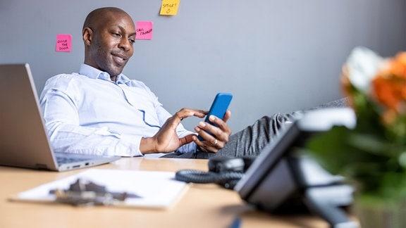 Mann (Unternehmer) sitzt mit Smartphone in der Hand und darauf blickend zufrieden am Schreibtisch mit Laptop, Telefon, Dokumenten, Vordergrund unscharf, Hintergrund mit Klebezetteln an der Wand.