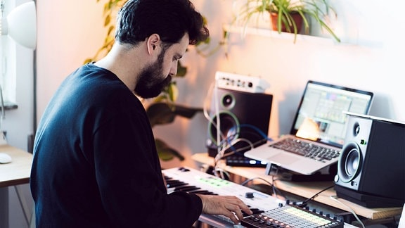 Mann sitzt im heimischen Musikstudio an Tasteninstrument und Mischpult, mit Laptop und Boxen. Aufnahme von schräg hinten, kontrastreiche Farben, Tiefenunschärfe.