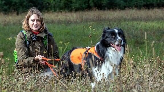 Ein Hund und eine Frau sind auf einer Wiese unterwegs