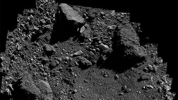 Diese Ansicht der Probenstelle Nightingale auf dem Asteroiden Bennu ist ein Mosaik von Bildern, die am 3. März vom OSIRIS-REx-Raumschiff der NASA gesammelt wurden. Die Probenstelle Nightingale befindet sich in dem relativ klaren Bereich direkt über der Mitte des Kraters - sichtbar in der Bildmitte. Der große, dunkle Felsbrocken oben rechts misst auf seiner längsten Achse 13 Meter. Das Mosaik wird so gedreht, dass Bennus Osten oben im Bild ist.