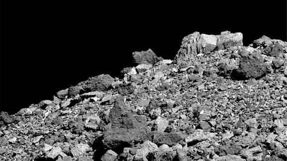Dieses Bild zeigt die große Vielfalt an Felsbrockenformen, -größen und -zusammensetzungen, die auf dem Asteroiden Bennu zu finden sind. Es wurde am 28. März von der PolyCam-Kamera auf dem OSIRIS-REx-Raumschiff der NASA aus einer Entfernung von 3,4 km aufgenommen. Das Sichtfeld beträgt 49,6 m. Für den Maßstab ist der große, helle Felsbrocken oben im Bild 4,8 m hoch.