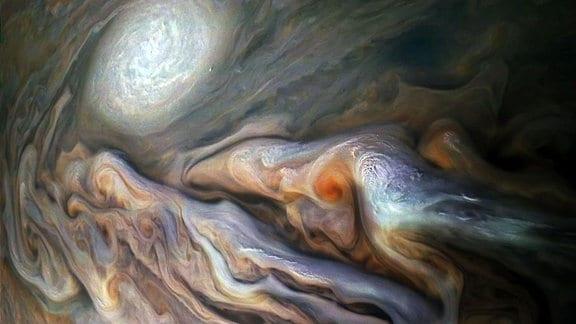 """Dieses Bild der NASA-Raumsonde Juno zeigt eine Vielzahl von prächtigen, wirbelnden Wolken in Jupiters dynamischem Nördlichen Temperaturgürtel. In der Szene sind mehrere hell-weiße """"Pop-up""""-Wolken sowie ein antizyklonaler Sturm zu sehen, der als weißes Oval bekannt ist."""