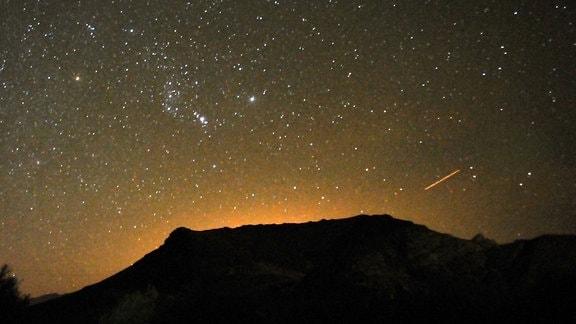 Ein Meteor streift über den Nachthimmel über der Geisterstadt Rhyolite in der Nähe von Las Vegas.