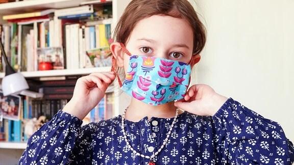 Die 5-jährige Lucia probiert beim Nähen von Mundschschutzmasken für den privaten Gebrauch eine Maske an.