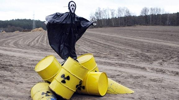 Figur des Todes auf Atommüllfässern