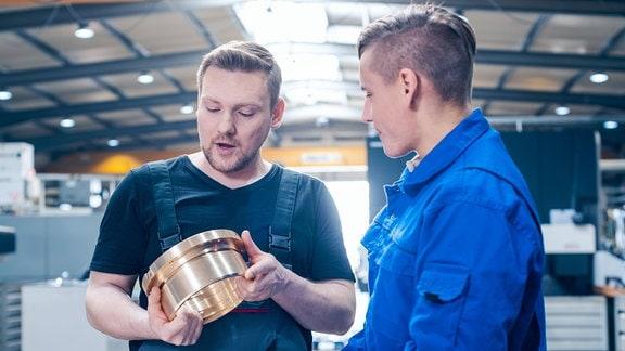 In junger Mann im Blaumann-Arbeitsanzug steht neben einem sprechenden Arbeiter oder Vorgesetzten in Latzhose in einer Werkhalle. Beide betrachten ein Werkstück, größerer golden glänzender Metallring wie von einem Rohr.