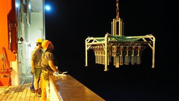 Menschen beobachten an Bord eines Schiffes ein Gerät, dass an einem Seil hängt